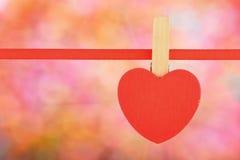 Η κόκκινη καρδιά στην κορδέλλα πέρα από φωτεινό ζωηρόχρωμο ακτινοβολεί θαμπάδα Στοκ Φωτογραφίες
