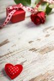 Η κόκκινη καρδιά, τυλιγμένο δώρο με την κορδέλλα και αυξήθηκε για την ημέρα βαλεντίνων, διάστημα αντιγράφων για το κείμενο Στοκ Εικόνες