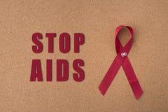Η κόκκινη κορδέλλα βοηθά την κορδέλλα στον πίνακα ανακοινώσεων με τη λέξη ενισχύσεων ` στάσεων ` Στοκ εικόνες με δικαίωμα ελεύθερης χρήσης