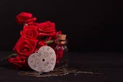 Η κόκκινη κορδέλλα αυξήθηκε, μπουκάλι γυαλιού και άχρονο ρολόι καρδιών με το μαύρο υπόβαθρο Στοκ εικόνα με δικαίωμα ελεύθερης χρήσης