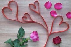 Η κόκκινη κορδέλλα μορφής καρδιών τέσσερα με το ροζ και κόκκινος αυξήθηκε στην ξύλινη επιφάνεια Στοκ εικόνα με δικαίωμα ελεύθερης χρήσης