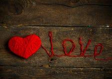 Η κόκκινη μορφή καρδιών με μια αγάπη επιγραφής έκανε από το μαλλί στο παλαιό s Στοκ φωτογραφία με δικαίωμα ελεύθερης χρήσης