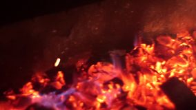 Η κόκκινη πυρκαγιά καίει το ξύλο στο σκοτάδι, τέφρα στην πυρκαγιά, κινηματογράφηση σε πρώτο πλάνο καυτοί άνθρακες για τον ορειχαλ απόθεμα βίντεο