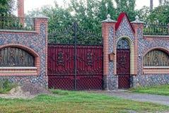 Η κόκκινη πύλη και μια πόρτα φιαγμένη από μέταλλο με ένα σφυρηλατημένο σχέδιο και μια πέτρα περιφράζουν μέσα την οδό Στοκ Εικόνες