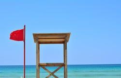 Η κόκκινη σημαία και το σπίτι του lifeguard Στοκ Εικόνα