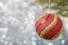 Η κόκκινη σφαίρα Χριστουγέννων σε έναν κλάδο χριστουγεννιάτικων δέντρων πέρα από το θολωμένο λαμπρό υπόβαθρο, κλείνει επάνω Στοκ εικόνα με δικαίωμα ελεύθερης χρήσης