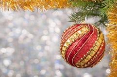Η κόκκινη σφαίρα Χριστουγέννων σε έναν κλάδο χριστουγεννιάτικων δέντρων πέρα από το θολωμένο λαμπρό υπόβαθρο, κλείνει επάνω Στοκ φωτογραφία με δικαίωμα ελεύθερης χρήσης