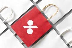 Η κόκκινη τσάντα αγορών από το ανακύκλωσης έγγραφο με τα τοις εκατό υπογράφει σε μια σειρά των άσπρων τσαντών αγορών στο γκρίζο υ Στοκ φωτογραφίες με δικαίωμα ελεύθερης χρήσης