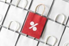 Η κόκκινη τσάντα αγορών από το ανακύκλωσης έγγραφο με τα τοις εκατό υπογράφει σε μια σειρά των άσπρων τσαντών αγορών στο γκρίζο υ Στοκ εικόνα με δικαίωμα ελεύθερης χρήσης