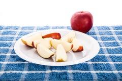 Η κόκκινη Apple με τις φέτες στο άσπρο πιάτο Στοκ Εικόνες