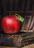 Η κόκκινη Apple με το πράσινο φύλλο στο παλαιό βιβλίο Στοκ φωτογραφία με δικαίωμα ελεύθερης χρήσης