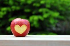 Η κόκκινη Apple με το σύμβολο καρδιών στον ξύλινο πίνακα πέρα από τη φύση Στοκ φωτογραφία με δικαίωμα ελεύθερης χρήσης