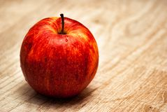 Η κόκκινη Apple σε ένα ξύλινο υπόβαθρο Στοκ Εικόνες