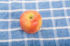 Η κόκκινη Apple στην μπλε πετσέτα Στοκ φωτογραφία με δικαίωμα ελεύθερης χρήσης