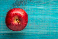 Η κόκκινη Apple στον εκλεκτής ποιότητας μπλε ξύλινο πίνακα Στοκ Εικόνες