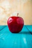 Η κόκκινη Apple στον εκλεκτής ποιότητας μπλε ξύλινο πίνακα Στοκ εικόνες με δικαίωμα ελεύθερης χρήσης