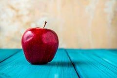 Η κόκκινη Apple στον εκλεκτής ποιότητας μπλε ξύλινο πίνακα Στοκ Εικόνα