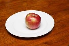 Η κόκκινη Apple στο άσπρο πιάτο Στοκ Φωτογραφία