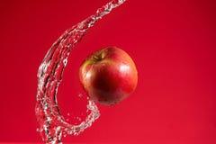 Η κόκκινη Apple στο κόκκινο υπόβαθρο Στοκ Εικόνες