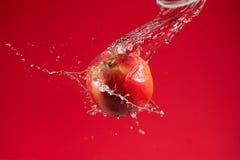 Η κόκκινη Apple στο κόκκινο υπόβαθρο Στοκ εικόνα με δικαίωμα ελεύθερης χρήσης