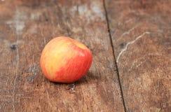 Η κόκκινη Apple στο ξύλινο υπόβαθρο, με το διάστημα αντιγράφων Στοκ Εικόνα