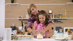 Η κόρη ζυμώνει τη ζύμη στην κουζίνα φιλμ μικρού μήκους