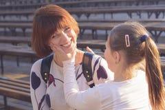 Η κόρη κοριτσιών λέει mom το χαμόγελο φωτογραφία που τονίζετα&i Στοκ Εικόνες