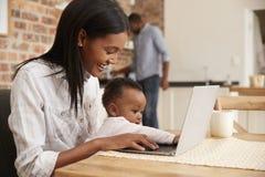 Η κόρη μητέρων και μωρών χρησιμοποιεί το lap-top δεδομένου ότι ο πατέρας προετοιμάζει το γεύμα Στοκ Φωτογραφία