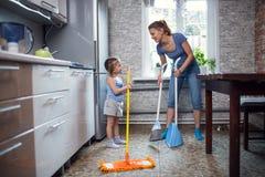 Η κόρη μητέρων πλένει το πάτωμα στο σπίτι Στοκ εικόνες με δικαίωμα ελεύθερης χρήσης