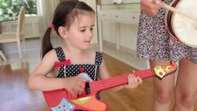 Η κόρη παίζει την κιθάρα παιχνιδιών και απόθεμα βίντεο