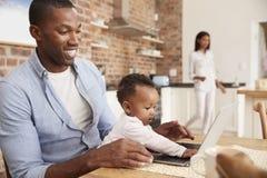 Η κόρη πατέρων και μωρών χρησιμοποιεί το lap-top δεδομένου ότι η μητέρα προετοιμάζει το γεύμα Στοκ εικόνα με δικαίωμα ελεύθερης χρήσης