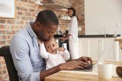 Η κόρη πατέρων και μωρών χρησιμοποιεί το lap-top δεδομένου ότι η μητέρα προετοιμάζει το γεύμα Στοκ Φωτογραφία