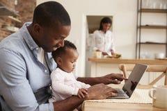 Η κόρη πατέρων και μωρών χρησιμοποιεί το lap-top δεδομένου ότι η μητέρα προετοιμάζει το γεύμα Στοκ φωτογραφία με δικαίωμα ελεύθερης χρήσης