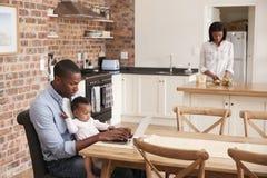 Η κόρη πατέρων και μωρών χρησιμοποιεί το lap-top δεδομένου ότι η μητέρα προετοιμάζει το γεύμα Στοκ Εικόνες