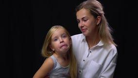 Η κόρη που κάνει ένα αστείο πρόσωπο καθμένος στις μητέρες περιτυλίγει φιλμ μικρού μήκους