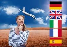 η κύρια γλώσσα σημαιοστολίζει κοντά στη νέα γυναίκα με το αεροπλάνο πίσω στον τομέα Στοκ φωτογραφία με δικαίωμα ελεύθερης χρήσης