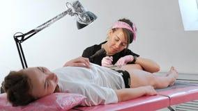 Η κύρια ελκυστική γυναίκα δερματοστιξιών με τα dreadlocks διαστίζει τον πελάτη στο κορίτσι στο ισχίο Μαύρα μηχανή και μελάνι δερμ φιλμ μικρού μήκους