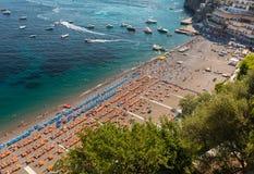 Η κύρια παραλία σε Positano, Spiaggia Grande, με τις φωτεινές πορτοκαλιές και μπλε ομπρέλες παραλιών του και τη λαμπιρίζοντας μπλ Στοκ Εικόνα
