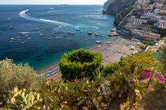 Η κύρια παραλία σε Positano, Spiaggia Grande, με τις φωτεινές πορτοκαλιές και μπλε ομπρέλες παραλιών του και τη λαμπιρίζοντας μπλ Στοκ Φωτογραφίες