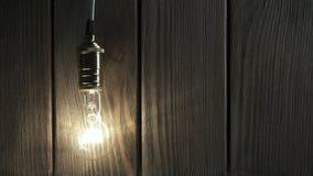 Η λάμπα φωτός φωτίζει στο ξύλινο υπόβαθρο απόθεμα βίντεο