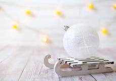 Η λάμποντας σφαίρα Χριστουγέννων στο ξύλινο έλκηθρο παιχνιδιών στο ελαφρύ υπόβαθρο bokeh με το αστέρι invitation new year ψαλιδίζ Στοκ Εικόνες