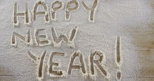 Η λέξη καλή χρονιά που γράφεται στο ψεκασμένο αλεύρι 4k φιλμ μικρού μήκους