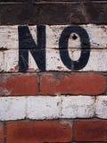 Η λέξη καμία που χρωματίζει σε έναν τουβλότοιχο Στοκ εικόνα με δικαίωμα ελεύθερης χρήσης