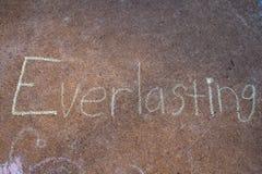 Η λέξη συνεχής που γράφει με την κιμωλία πεζοδρομίων στο γκρίζο υπόβαθρο συγκεκριμένων πεζοδρομίων στοκ φωτογραφία