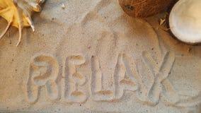 η λέξη χαλαρώνει στην άμμο με το θαλασσινό κοχύλι και την καρύδα Στοκ Φωτογραφία