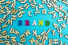"""Η λέξη """"εμπορικό σήμα """"είναι ευθυγραμμισμένη με τις πολύχρωμες επιστολές σε ένα μπλε υπόβαθρο στοκ εικόνα με δικαίωμα ελεύθερης χρήσης"""