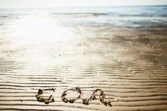 Η λέξη Goa γράφεται στην άμμο θαλασσίως Ίχνος στην παραλία Εκροή της θάλασσας Στοκ Εικόνες