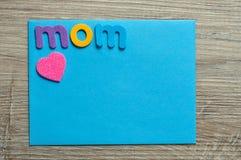 Η λέξη mom με μια ρόδινη καρδιά σε μια μπλε σημείωση Στοκ φωτογραφία με δικαίωμα ελεύθερης χρήσης