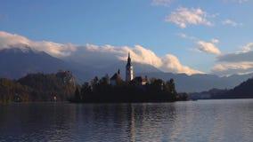 Η λίμνη αιμορράγησε με την εκκλησία του ST Marys της υπόθεσης στο μικρό νησί στο ηλιοβασίλεμα  Αιμορραγημένος, Σλοβενία, Ευρώπη φιλμ μικρού μήκους