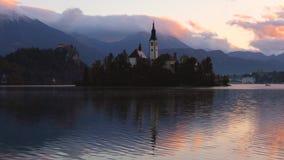 Η λίμνη αιμορράγησε, Σλοβενία με την εκκλησία του ST Marys της υπόθεσης στο μικρό νησί στο νερό και το όμορφο ηλιοβασίλεμα φιλμ μικρού μήκους
